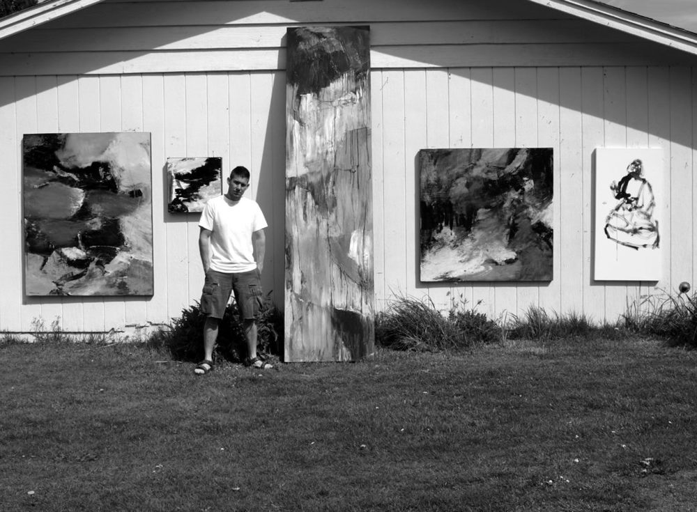 Christopher with paintings on outside studio wall.