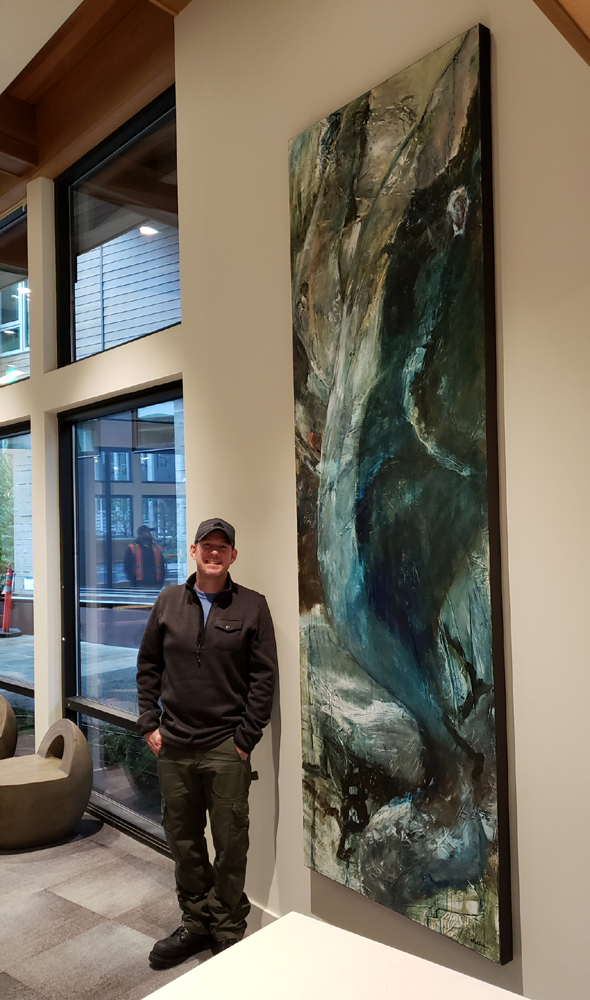 "Mathie standing with ""Celebration of Natural Power — Whale in Full Breach,"" 108 x 36 inches.   As installed in the lobby of Sitka Apartments, South Lake Union, Seattle, WA.   *SOLD  — thank you!"