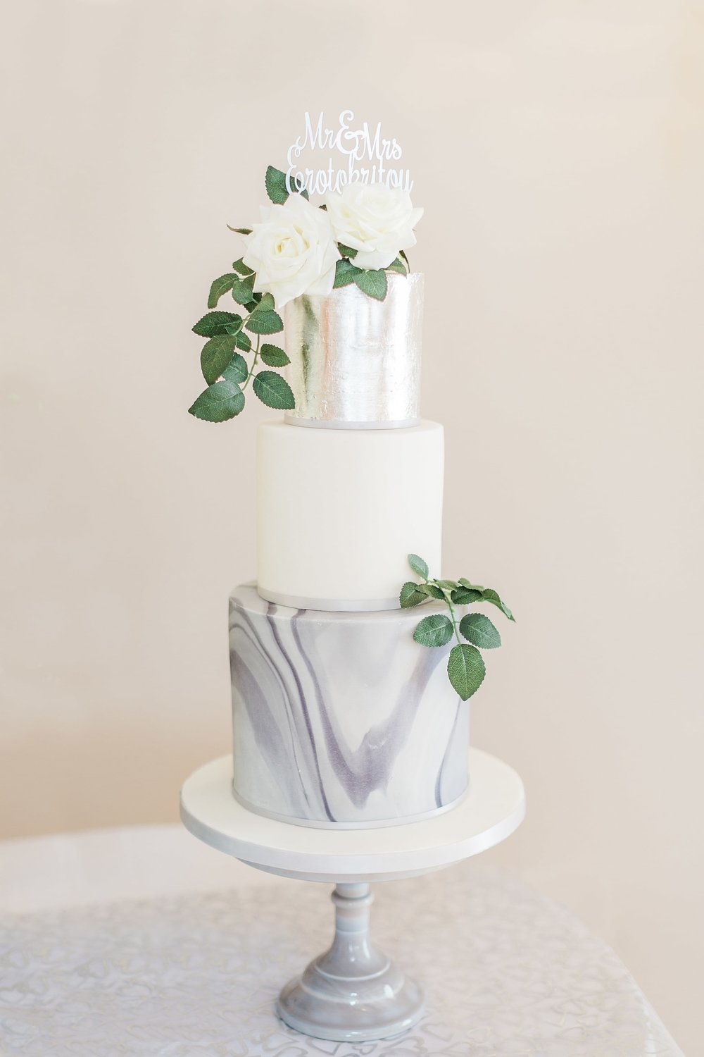 Modern wedding cake marble grey and white, and silver leaf dressed with white flowers and greenery. Cake by Hertfordshire wedding cake company Meadowsweet Cakes, photography by Sung Blue Photo