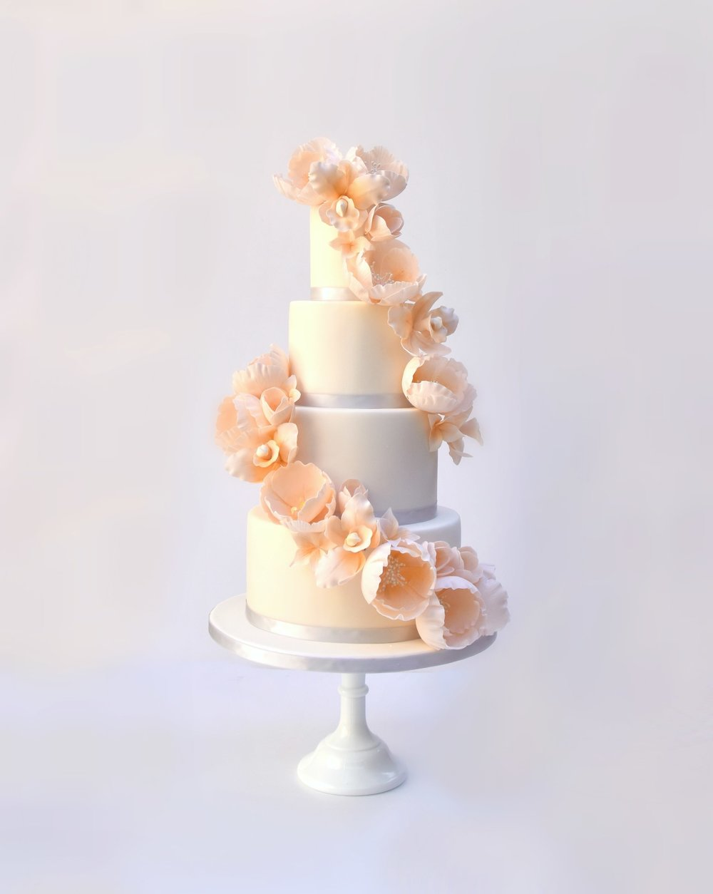 Showstopping wedding cake dressed with sugar flower cascade in pastel coral by wedding cake designer Meadowsweet Cakes