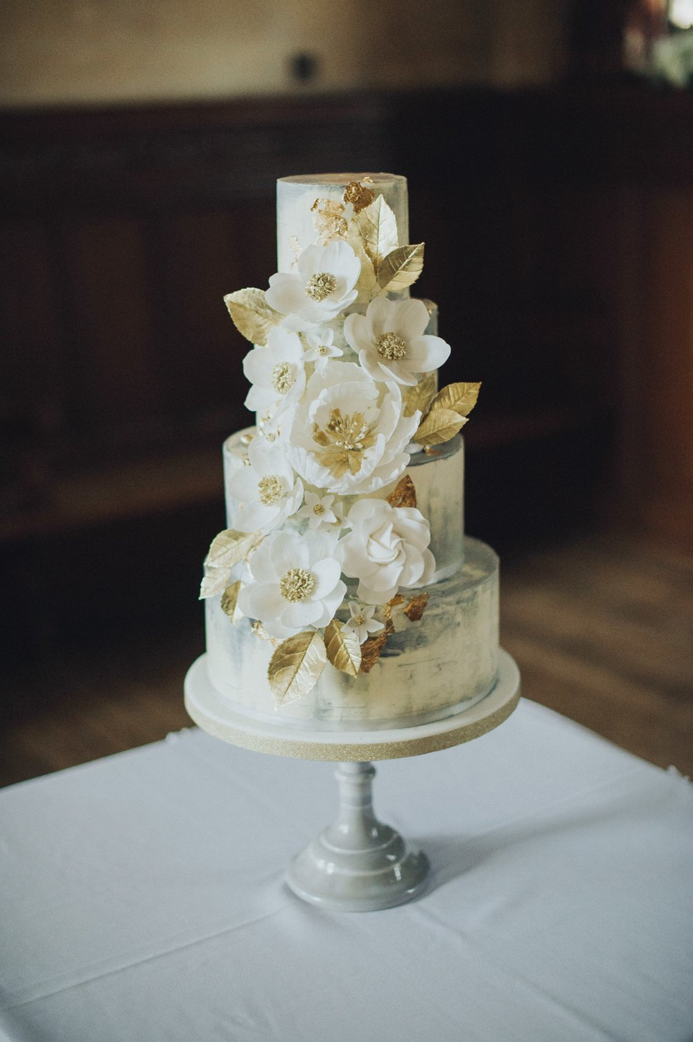 Fanhams Hall wedding cake concrete buttercream, sugar flowers, gold leaf and guilded leaves by Meadowsweet Cakes