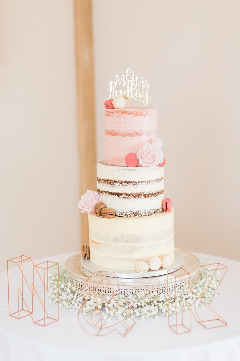 Beautiful semi naked wedding cake design, dressed with macarons and sugar roses. By Meadowsweet Cakes. Photography by Sung Blue Photo. Bassmead Manor Barns
