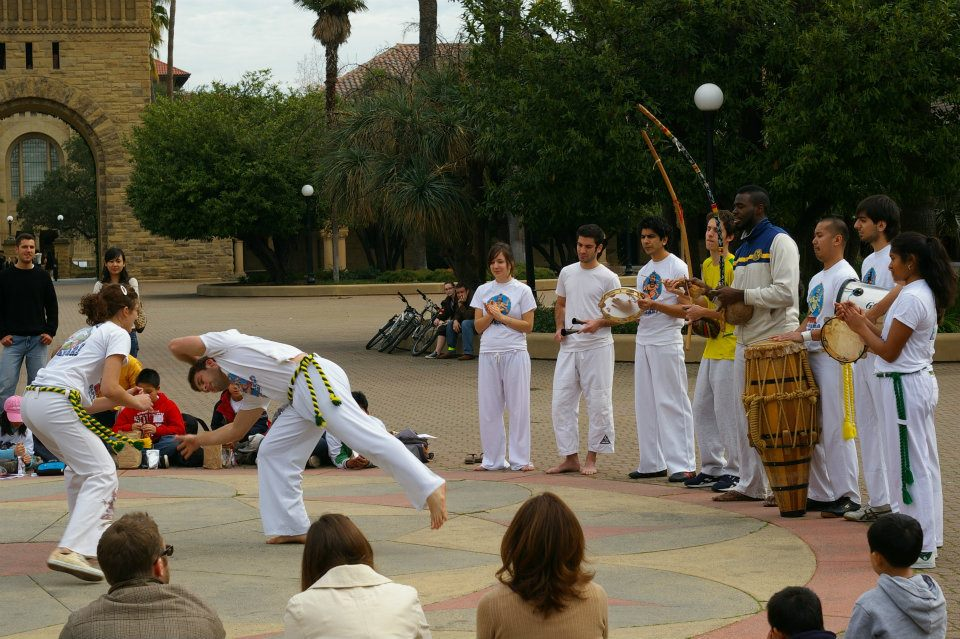 Capoeira roda at Stanford University - you see two berimbaus, two pandeiros (they look like tambourines), one agogô double-bell, and the atabaque drum.