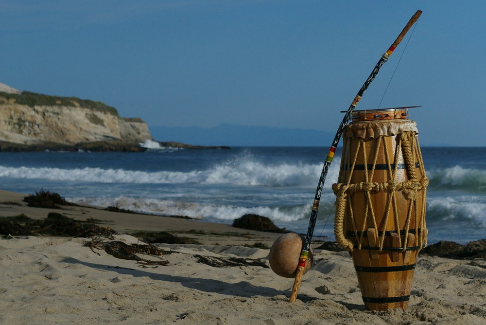 A berimbau leans against the atabaque drum, and a pandeiro rests on top.