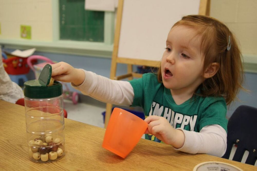 """Cheesy"" Beads - a fine motor activity made from a recycled parmesan container"