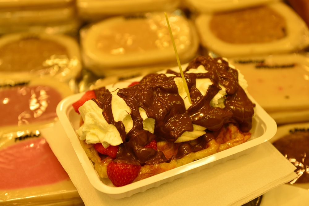 Sugar coated waffle with melted nutella, strawberries, bananas, and whipped cream.