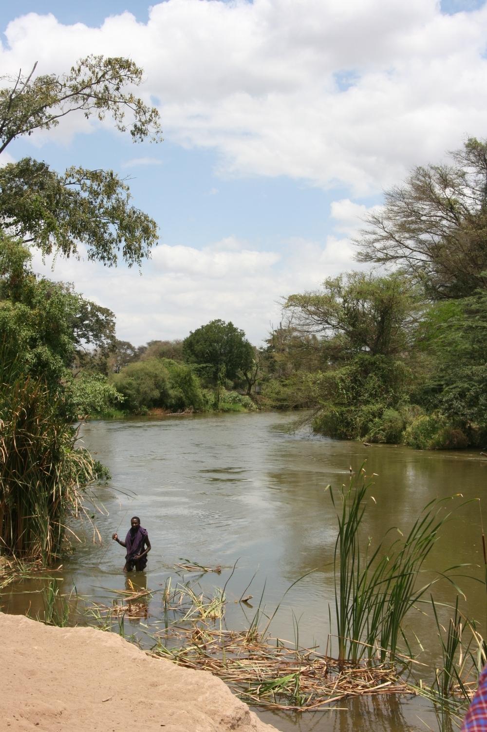 A man wades through the Pangani River while fishing - Tanzania