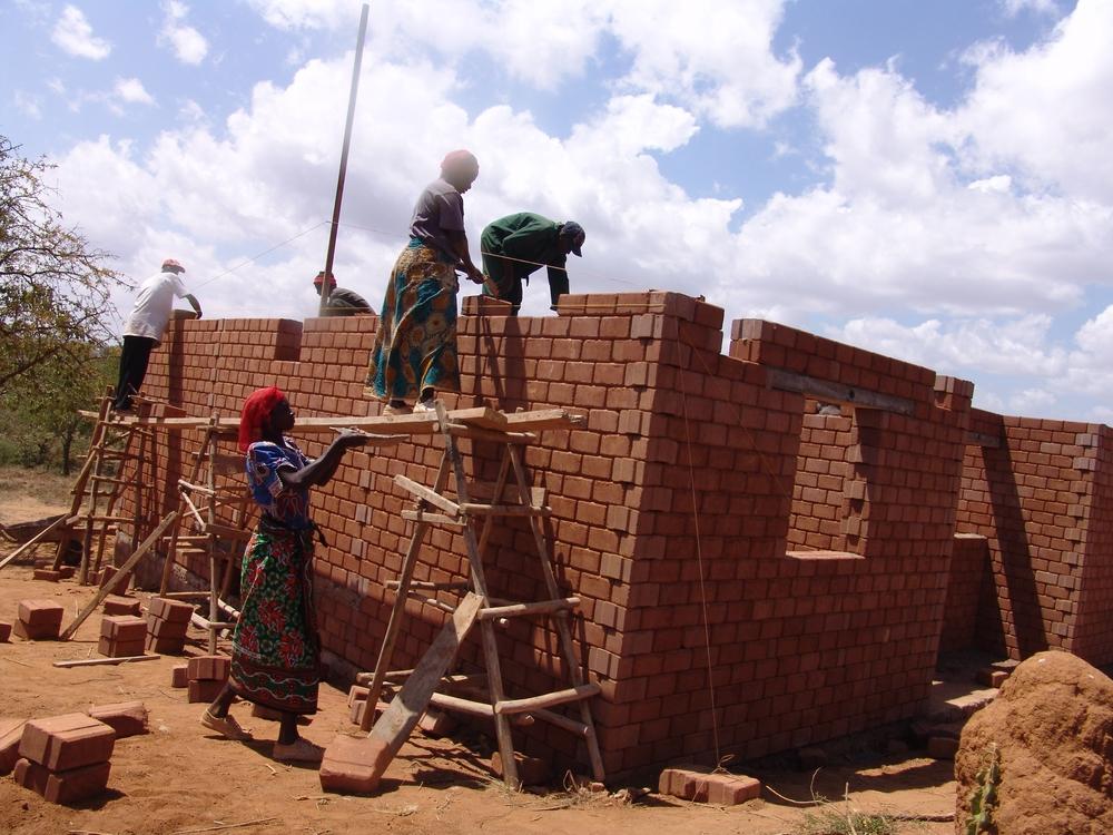 Local community members help build a new family home - Kenya
