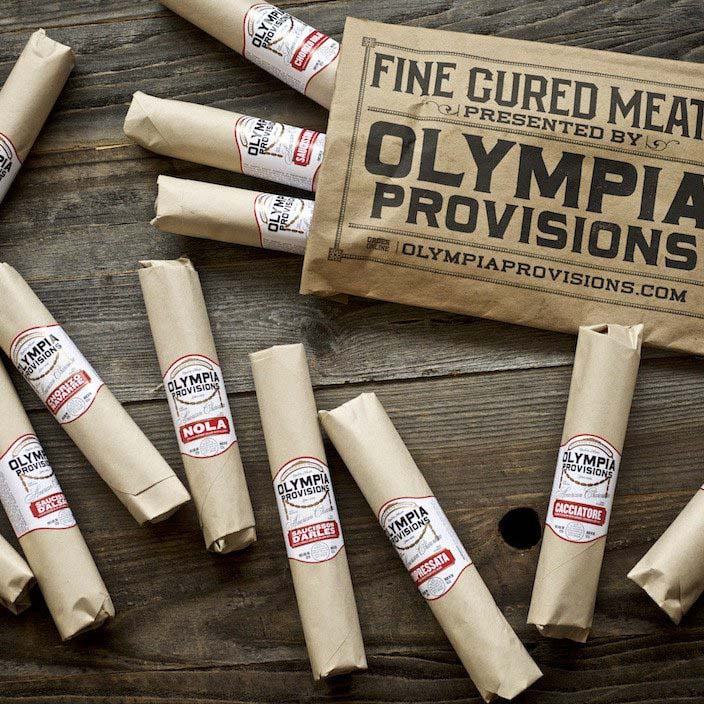 Olympia Provisions - Salumist Elias Cairo, grew up first generation Greek-American with a father who made charcuterie at home. Doing things the old-fashioned way was commonplace. Elias later journeyed to Europe to apprentice in the kitchens of masters. It was there that he rediscovered the art of curing meat and found inspiration in the markets and mountain towns of the old world.Back in beautiful Portland, Oregon, Elias set out to approach the craft of charcuterie with purity and patience, recreating a nearly extinct traditional technique that is seldom seen in America.The result is Olympia Provisions, Oregon's first USDA-approved salumeria, established in 2009, deeply rooted in the past.