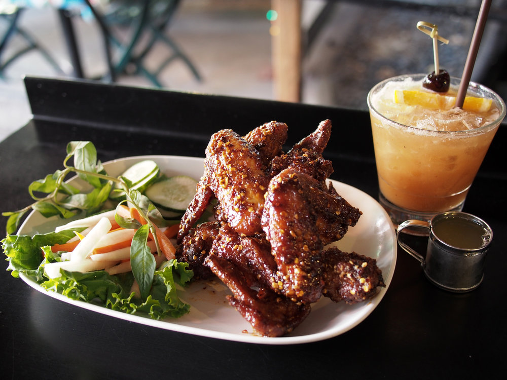 Fish sauce fried wings and a tamarind whiskey sour from Pok Pok Portland. There's also much discussion about how much credit he gives to the line chef who brought these wings onto the menu and their Vietnamese culinary heritage in comparison to how much of a featured dish they are.