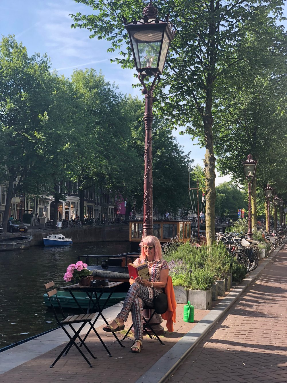 Reading in Amsterdam by a canal
