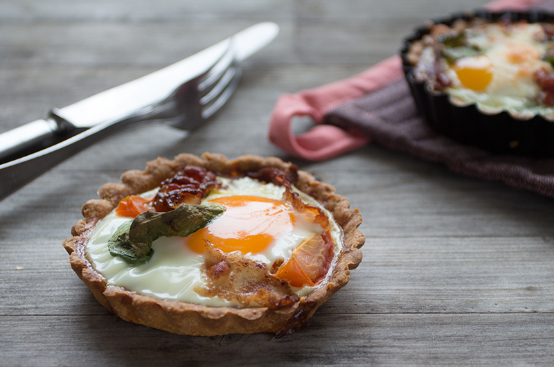 I disse små paiene har jeg samlet alt det beste fra en frokost: en god og knasende bunn, pesto, tomater, egg og bacon! Foto: Julia Edin