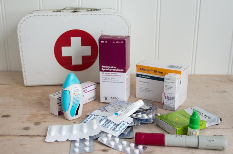 Førstehjelps-kofferten i bakgrunn. ALT foran er gamle medisiner som har gått ut på dato og som skal leveres til apoteket.