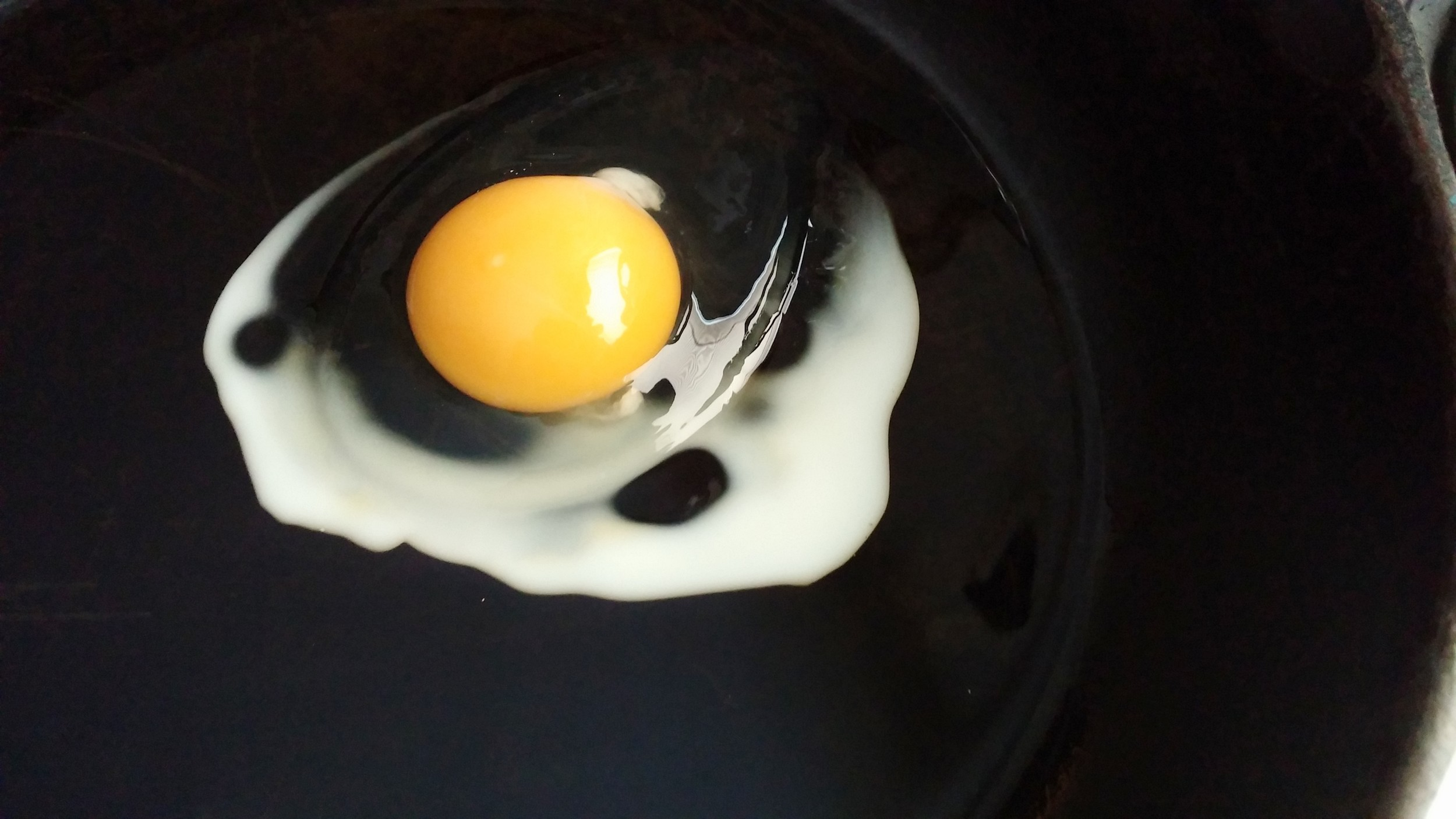 slowly frying an egg in oil