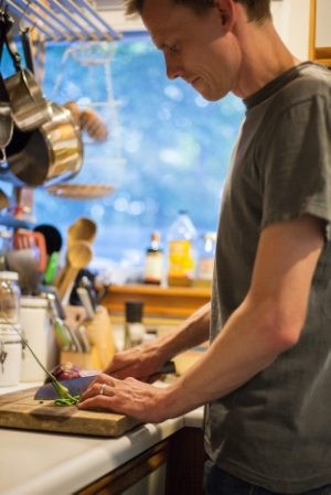Nate cutting garlic scapes. Photo Courtesy of Heidi Bagley.