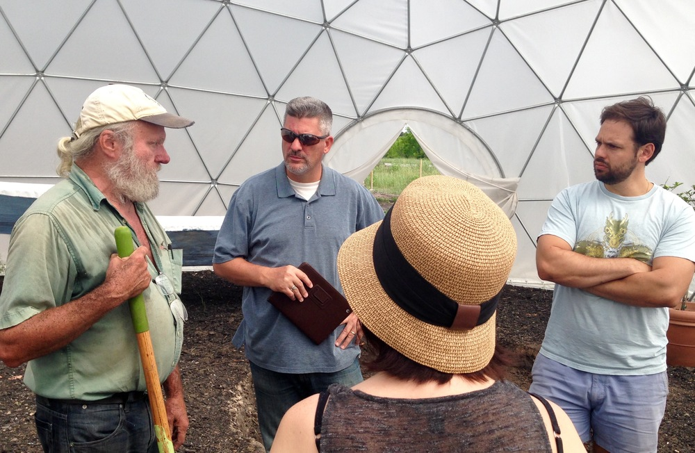 Mike (far left), explains to a tour group at Community First! his role in creating sustainable agriculture