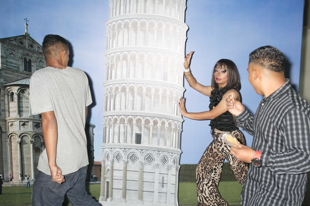 NadiA poses with the Leaning Tower of Pisa for her friends while out drinking at a promotional event. This image was taken moments before a man threw a chair at her from across the room. NadiA regularly suffers from this kind of harassment but she is determined to not let it cripple her.
