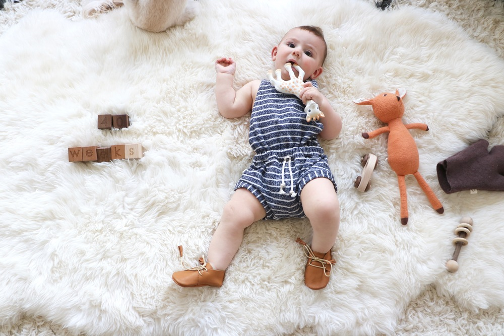 Noam is wearing a  Childhoods Clothing romper  and  Little Pine Outfitter Scout moccasins . Our blocks are from  Little Sapling Toys  and his fawn doll is  Hazel Village .