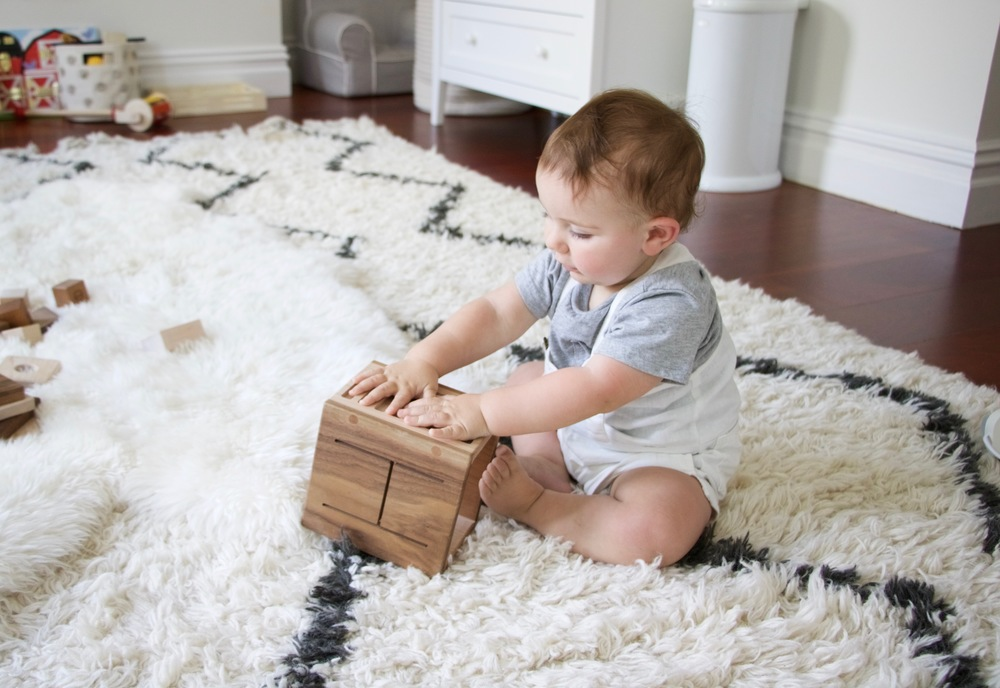 Noam playing with his  wooden drum .