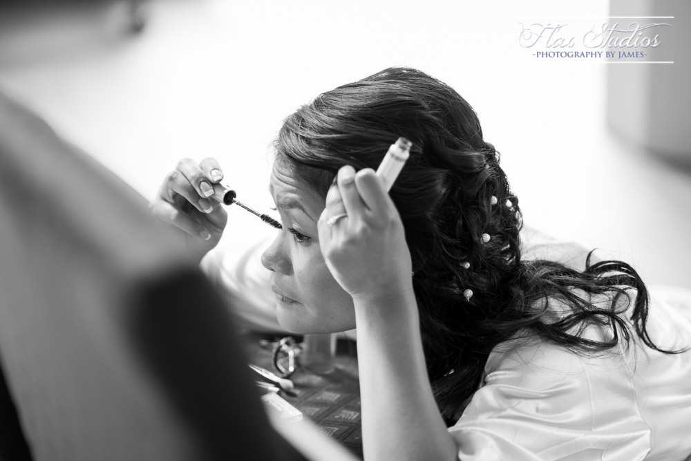 Bride applying wedding makeup