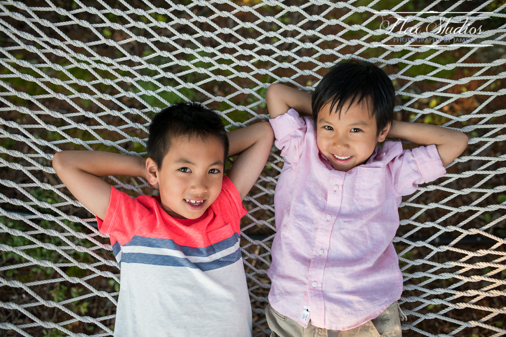 Brothers playing on a hammock