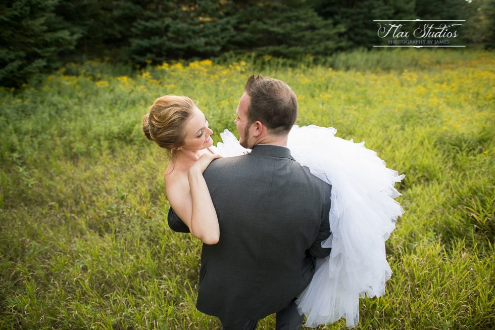 Groom carrying bride through fields Maine Weddings