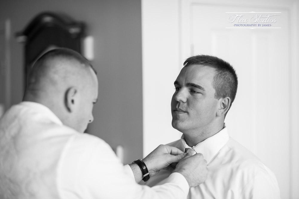 Groomsmen assisting groom getting ready