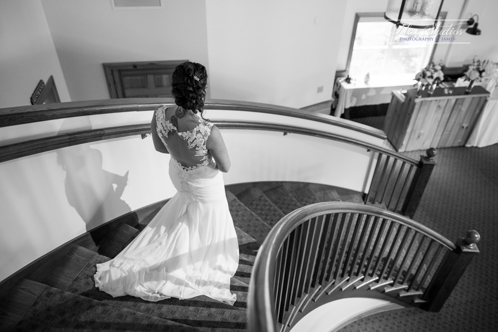 bride walking down the stairs at spruce point inn wedding