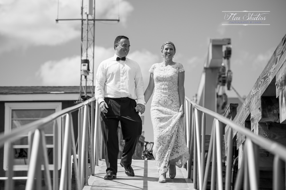 bride and groom walking on a pier