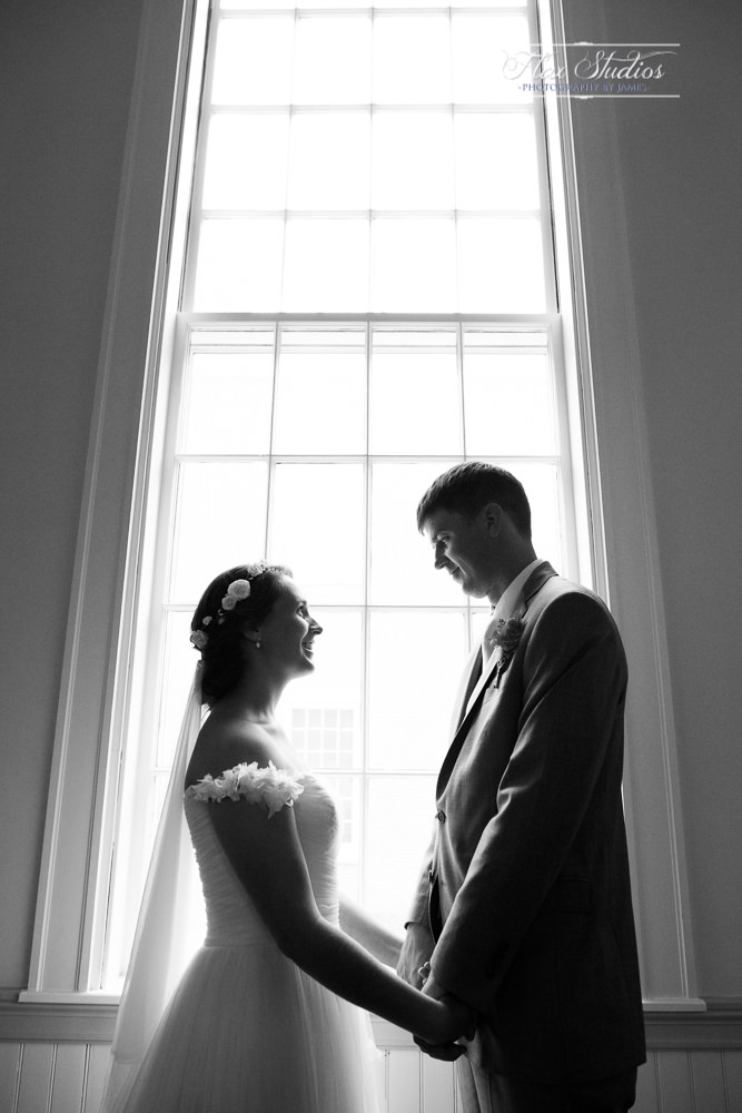 black and white wedding photo in front of windows