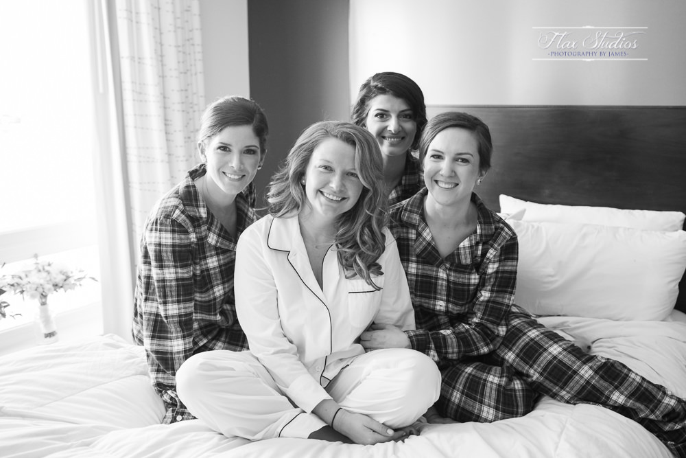 bride with bridesmaids on a bed with pjs