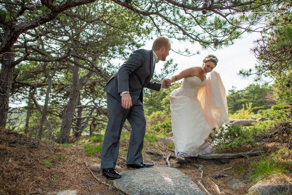 helping his bride on the rocks