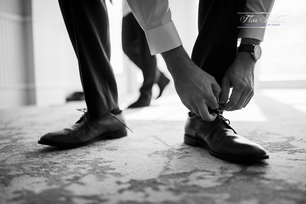 groom putting on his wedding attire