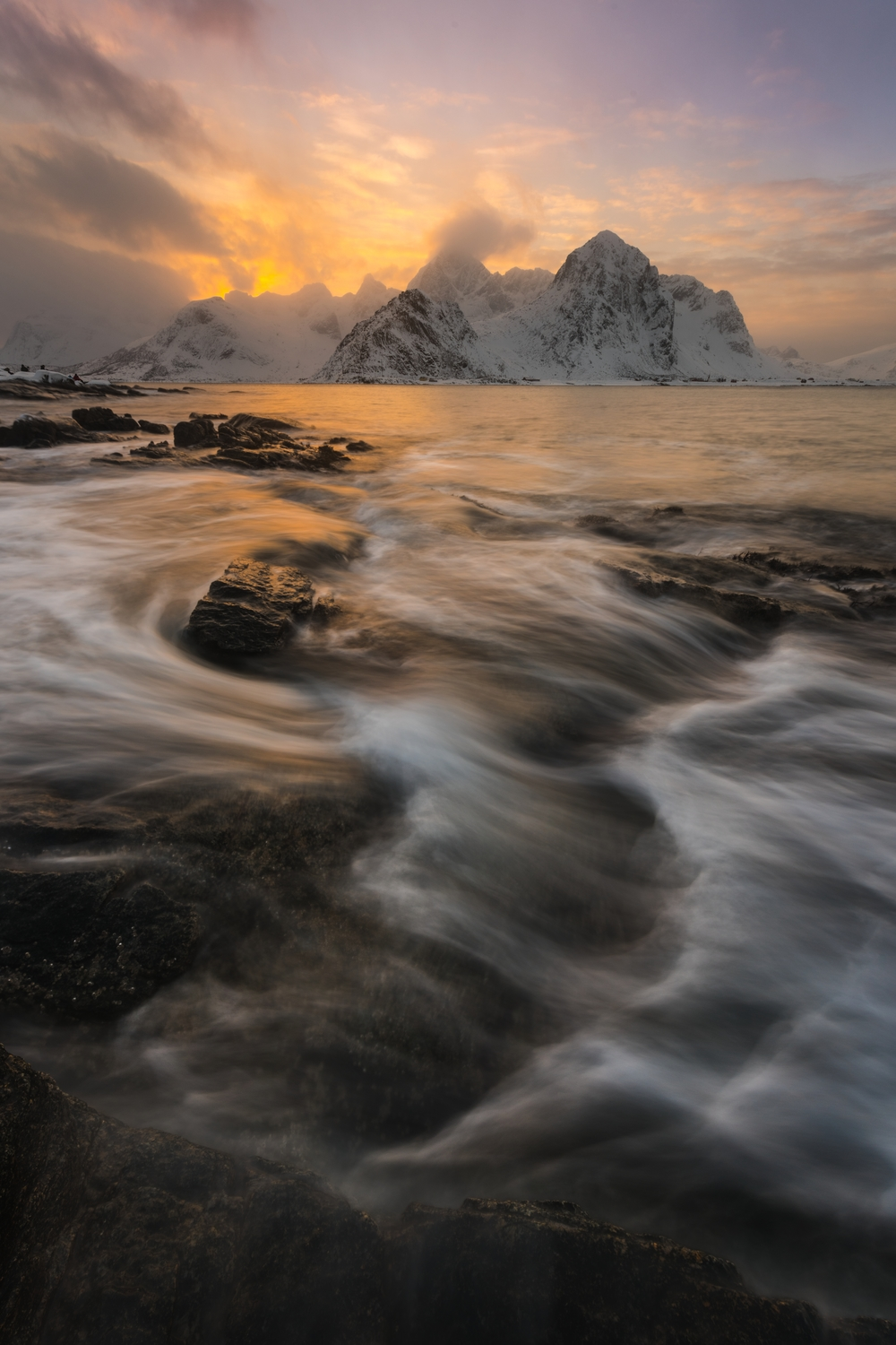 Dramatic clouds and cascades of waves crushing over the rocky beach of Vareid, Lofoten.  Click  here  to by prints of this photo.
