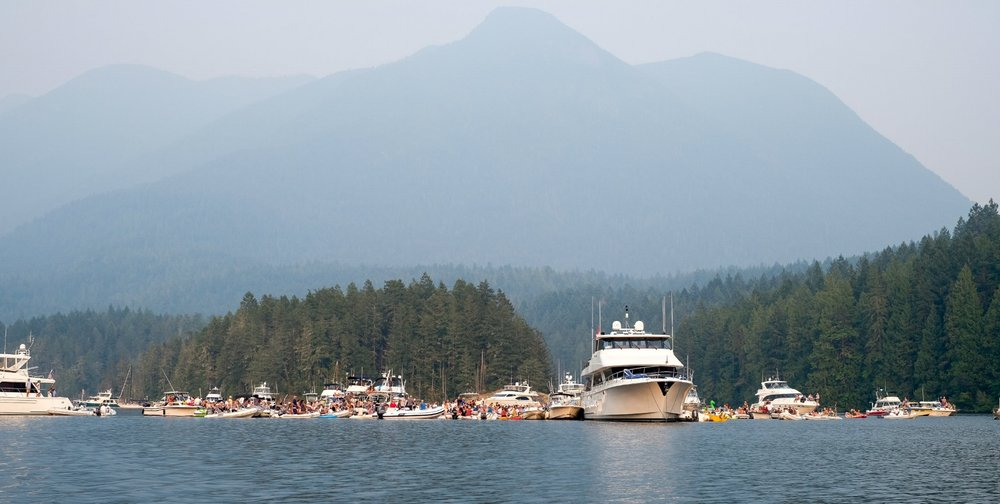 Several hundred people gather for the fifth annual Dinghy Concert in Prideaux Haven, Desolation Sound.  Live music played off the stern of an 80 foot yacht on this Saturday evening.  Image by Totes and the City for Destination: Desolation.