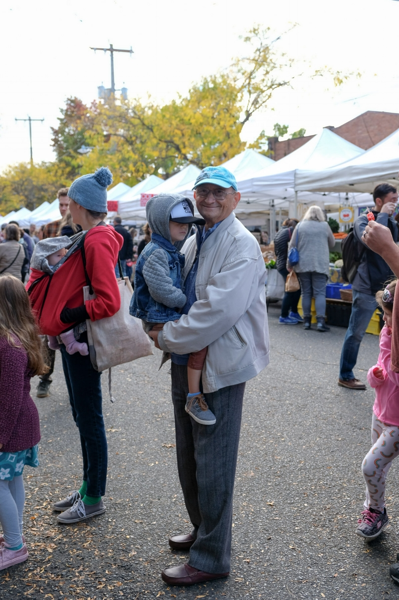 Totes and Nonno pose for a photo while waiting in line for the face painting booth at the Ballard Farmer's Market