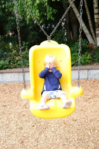 Apple sits in a bright yellow toddler swing at Webster Park in the Ballard Neighborhood of Seattle, Washington. | Exploring Seattle by Totes and the City