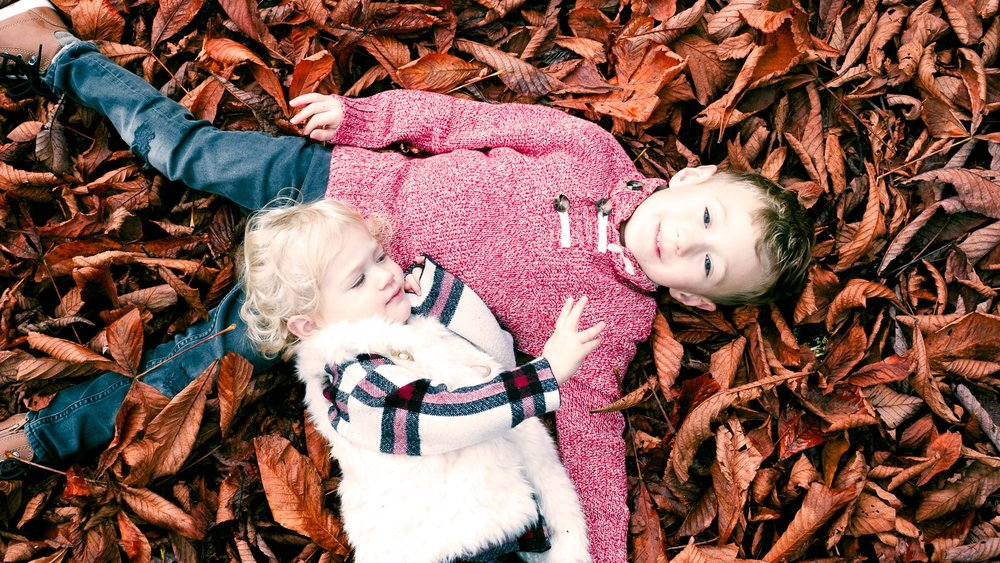 Totes and Apple lay lovingly in the fall leaves at Woodland Park in Seattle, Washington. Click to see the original photo and why the perfect photo isn't always what it seems! | By Totes and the City