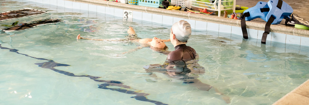 Totes floats on his back in starfish with the help of Coach Kat at Swim Guru in Seattle, Washington during on of his swim lessons.