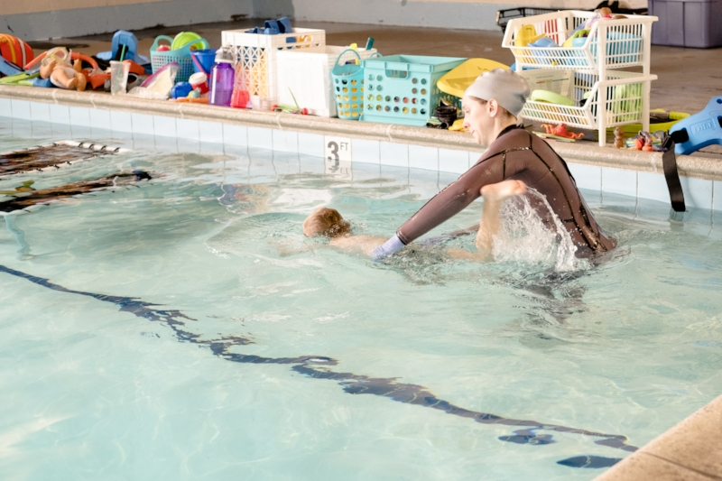Totes swims with Coach Kat's assistance during one of his swim lesson at Swim Guru.
