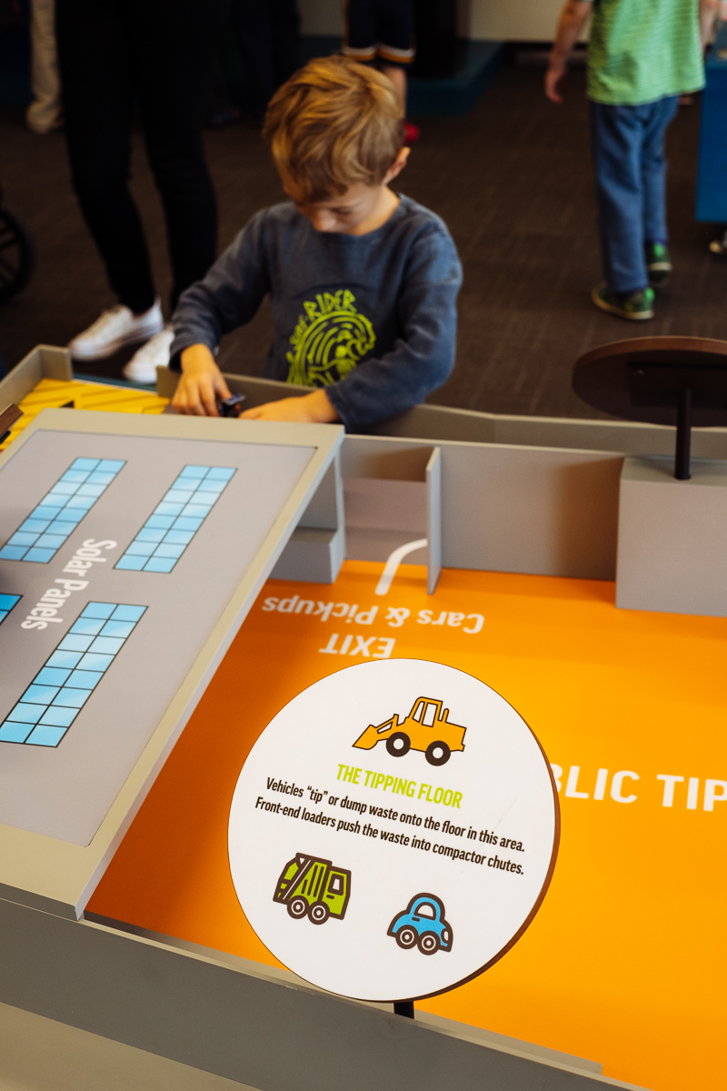 Totes and Apple play in the Community viewing room at the North Transfer Station in Seattle with miniature scale models of the tipping floor and other processes of the facility.