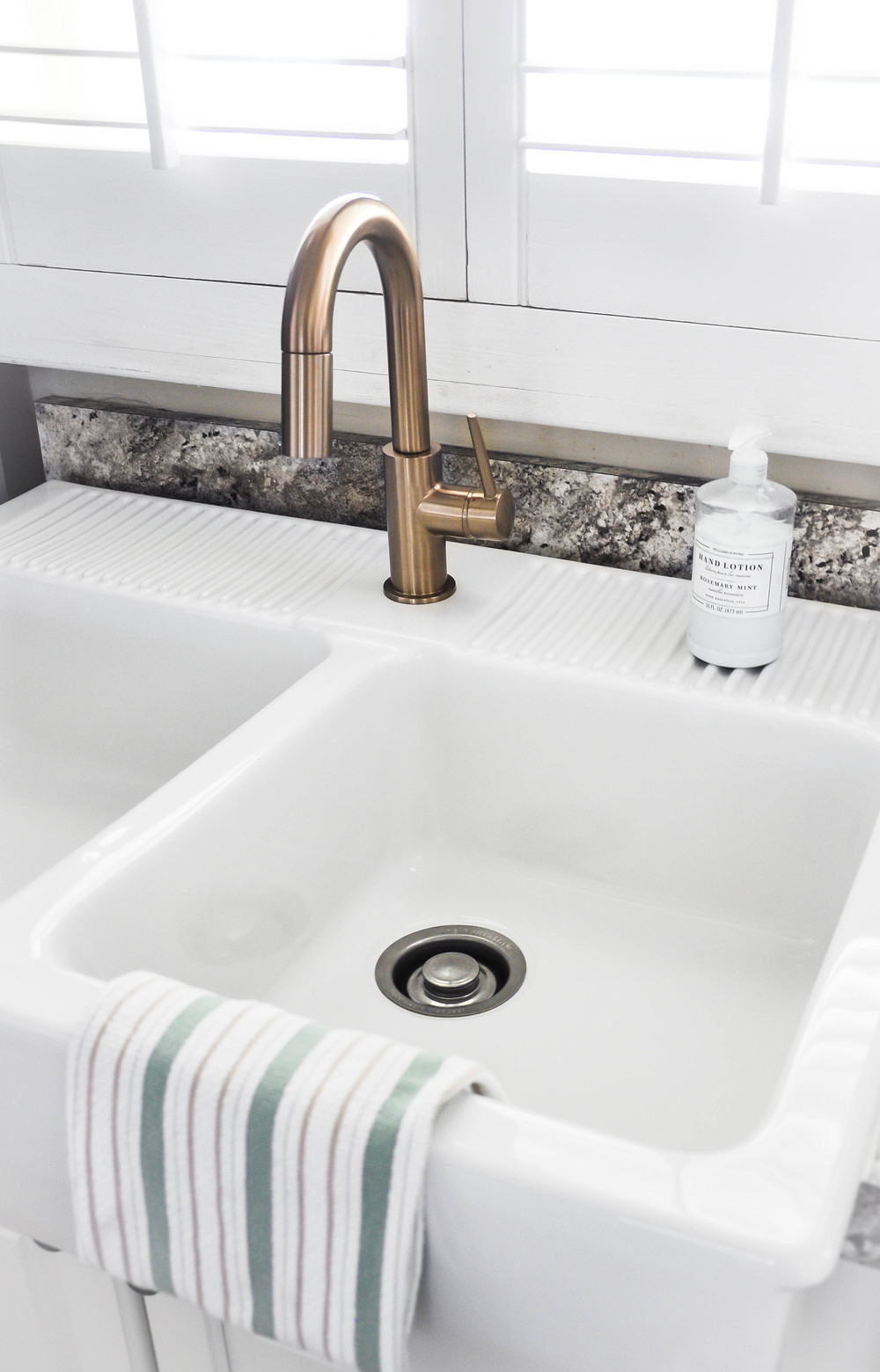 white kitchen sink with dishrag