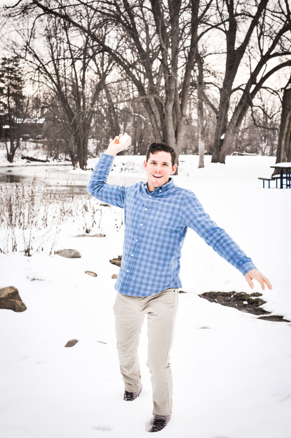Man in blue shirt throwing snowball