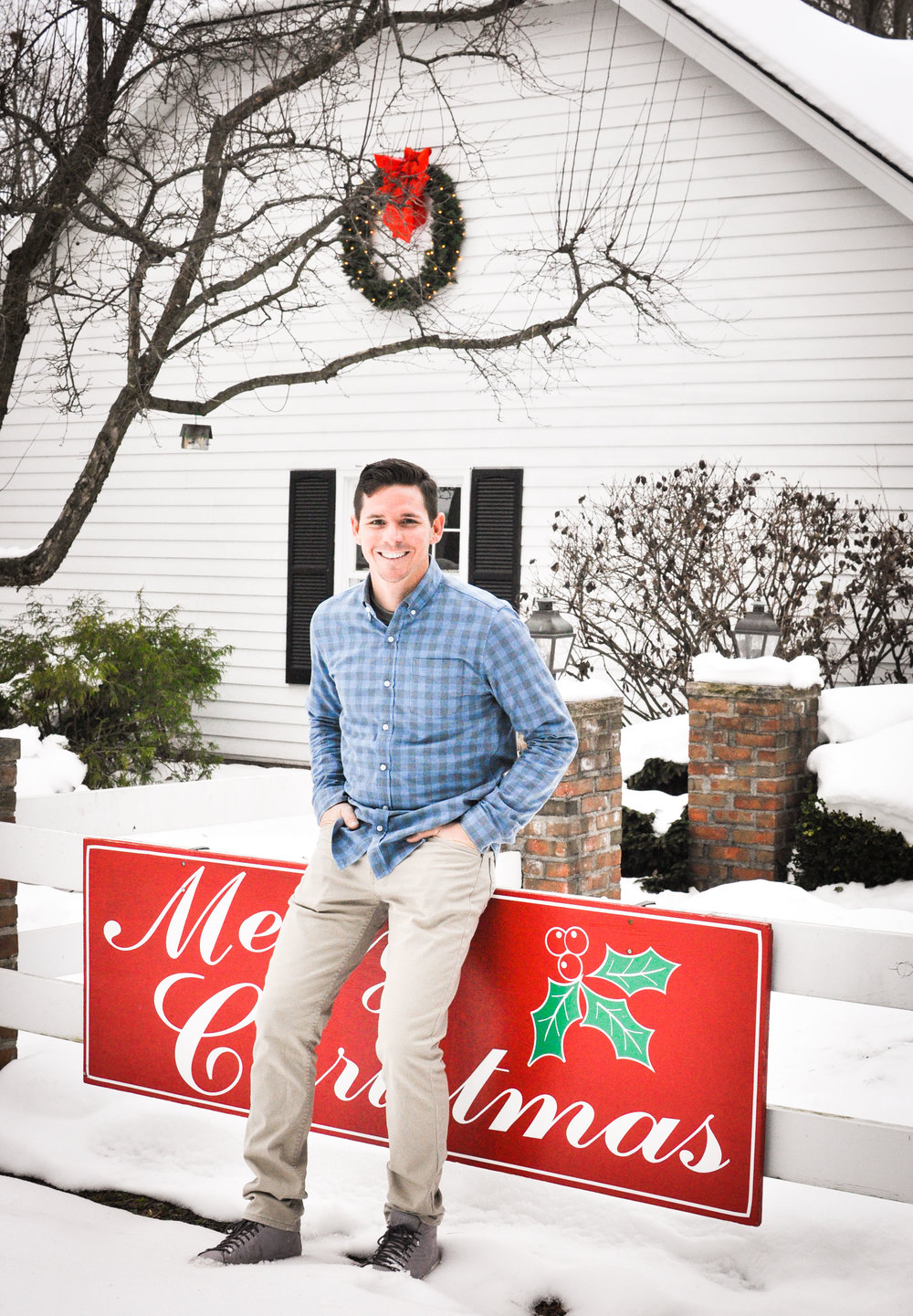 Man in front of house in snow at Christmas