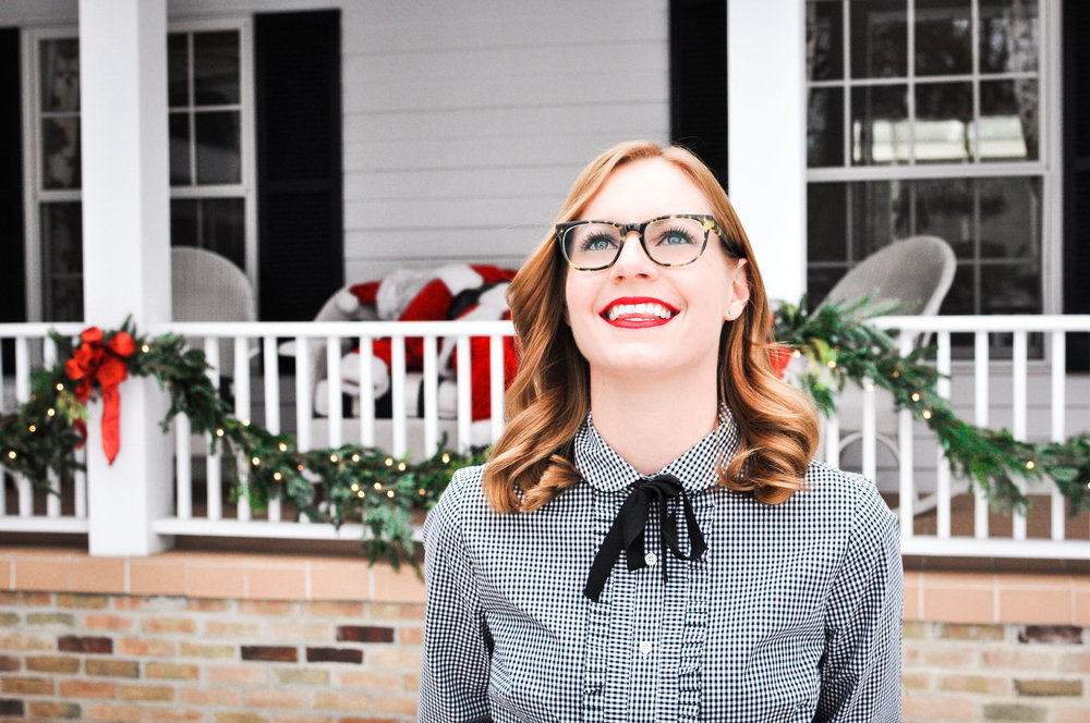 Woman in front of house decorated for Christmas in Michigan