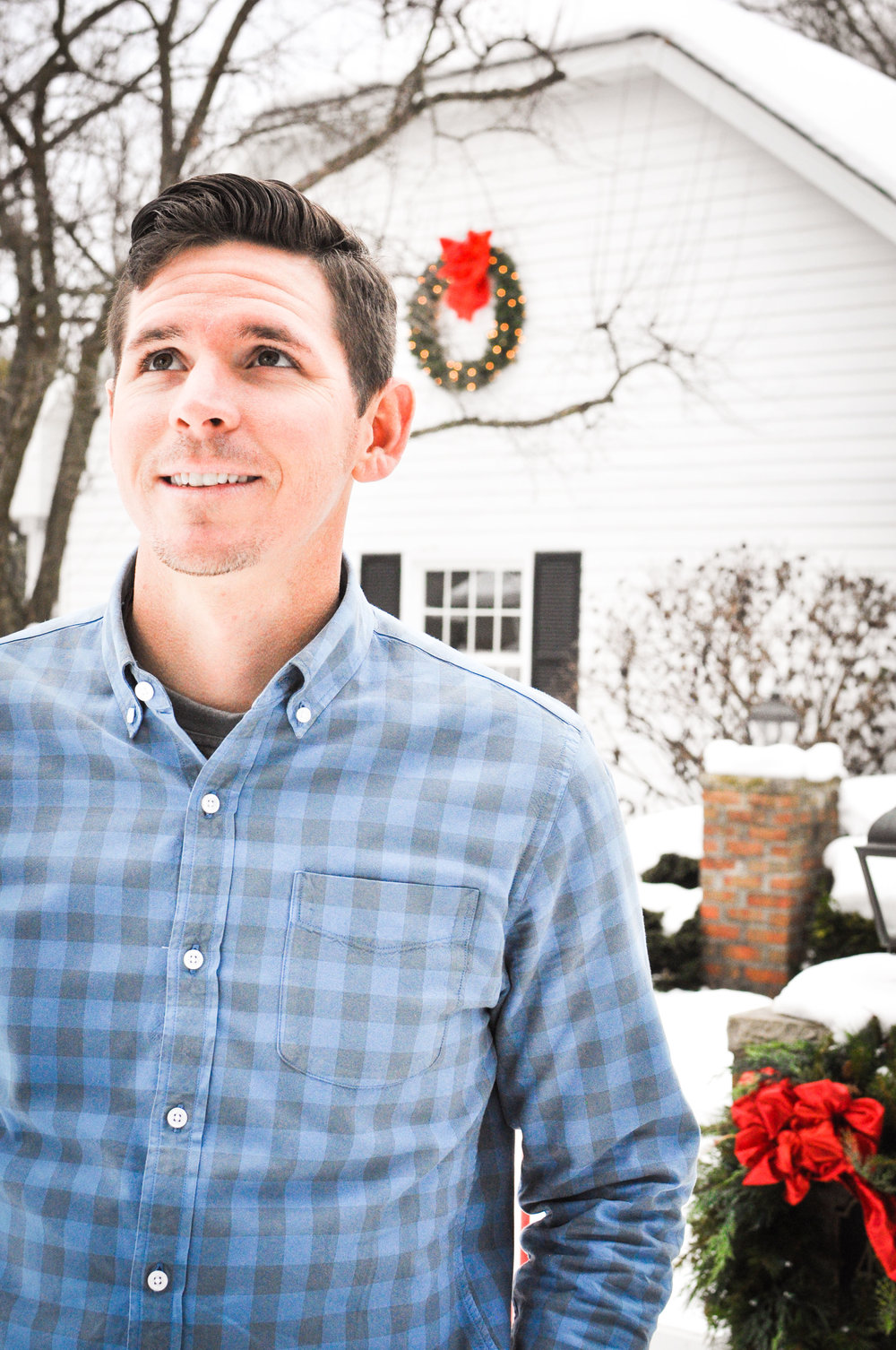 Man in front of Christmas house in blue shirt