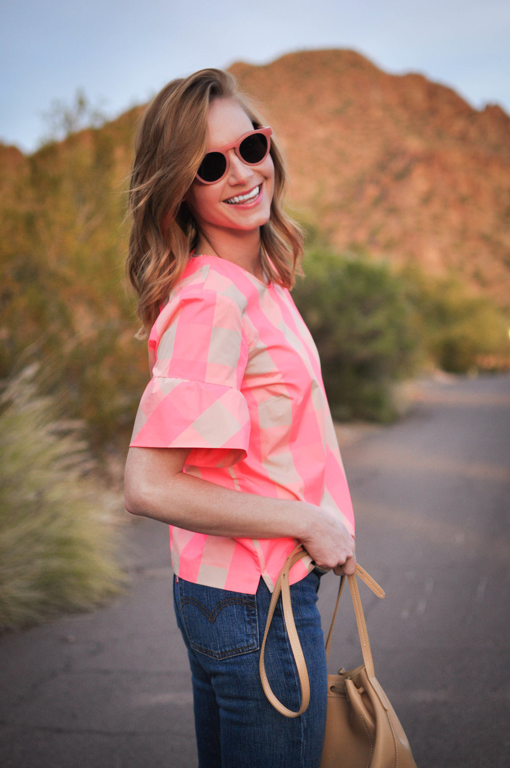 Smiling woman in pink sunglasses and top