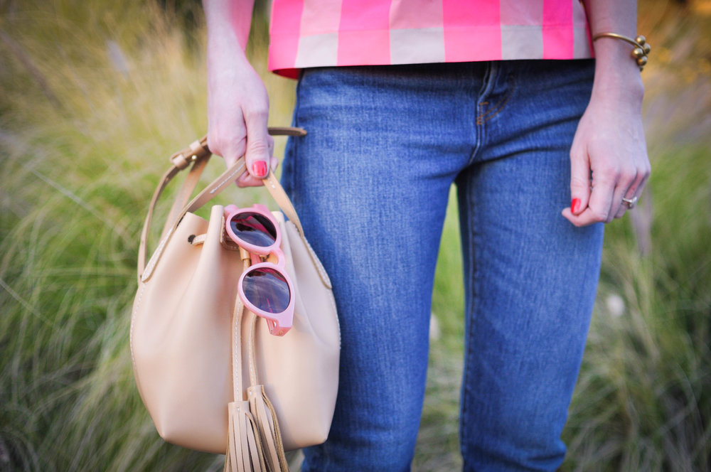 woman in jeans beige bag sunglasses