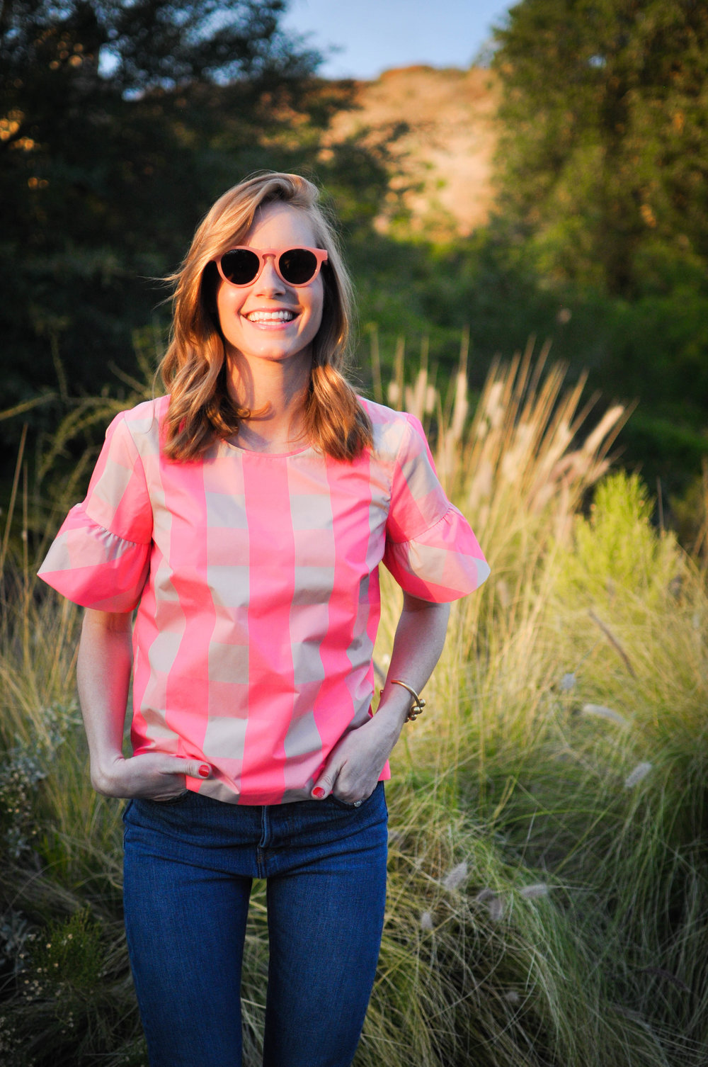 Woman in pink top and sunglasses smiling