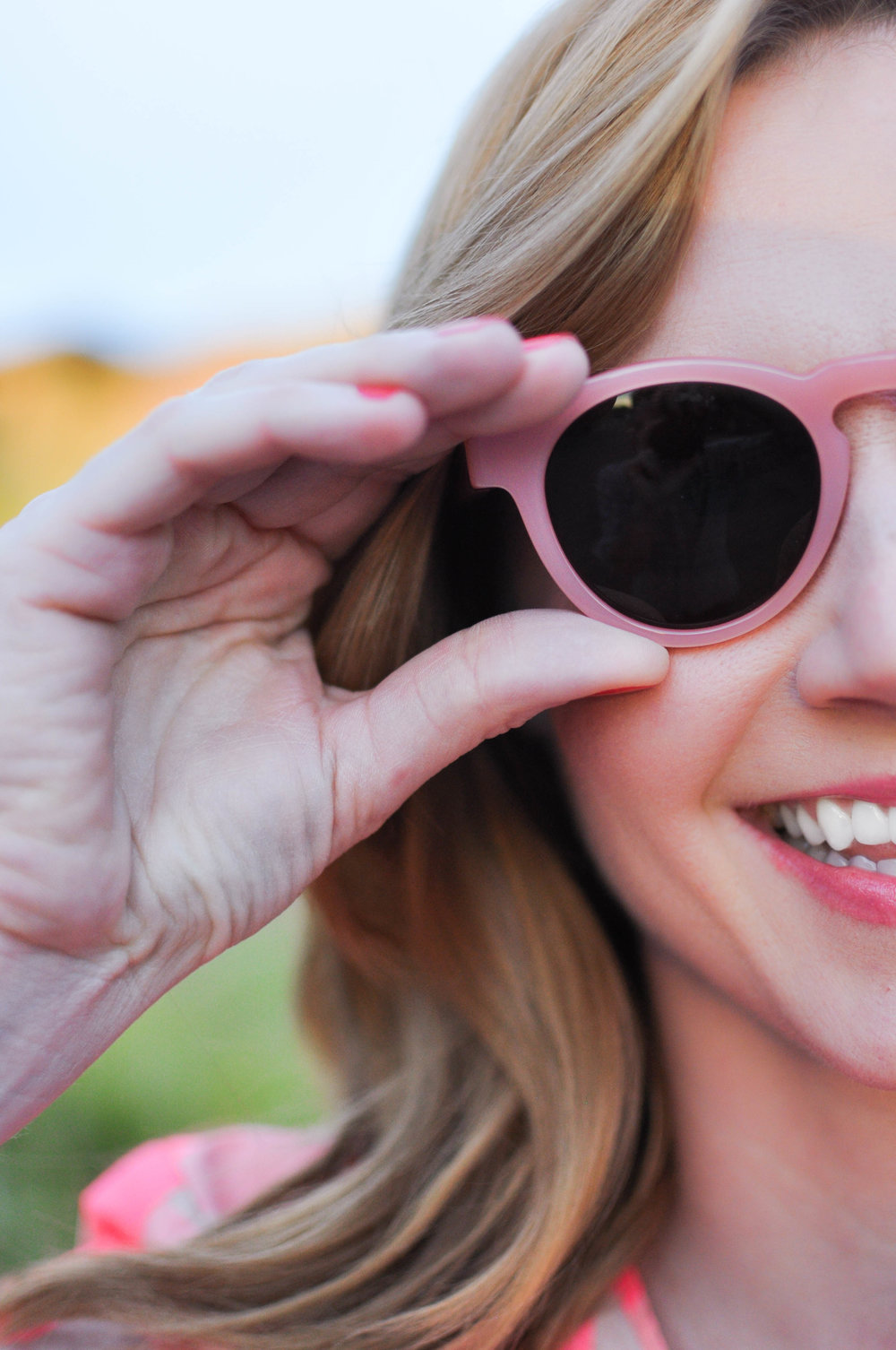closeup of woman's smiling face in pink-rimmed sunglasses